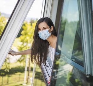 Junge Frau mit Maske beim Öffnen eines Wohnungsfensters