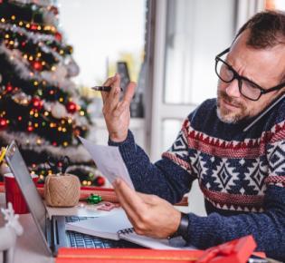 Arbeitender Mann inmitten von Weihnachtsdekoration