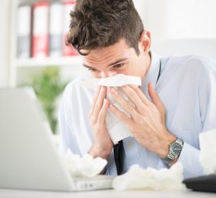 Erkälteter Mann im Büro