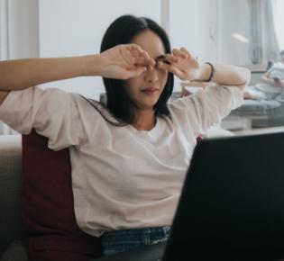 Frau am Computer reibt sich die Augen