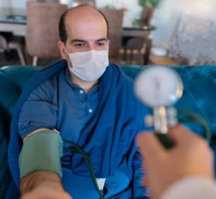 Blutdruckmessung an einem Mann mit Mundschutz