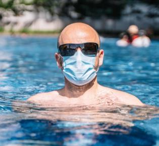 Mann mit Atemschutzmaske im Pool