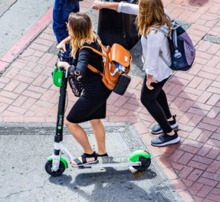 Schülerin mit E-Scooter an einer Ampelanlage