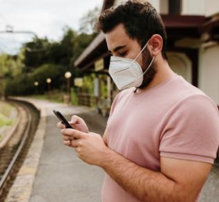 Wartender Bahnpendler mit FFP2-Maske
