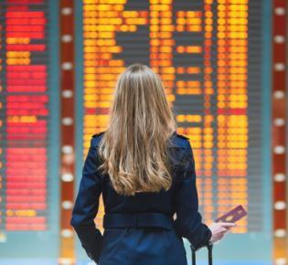 Junge Frau vor Flight Information Display System eines internationalen Flughafens