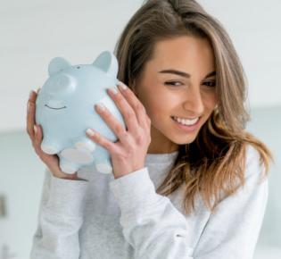 Junge Frau schüttelt Sparschwein