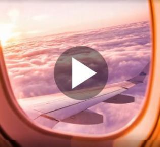 Blick aus einem Flugzeugfenster auf Trgfläche und Wolkendecke