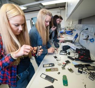 Jugendliche montieren ausgediente Handys auseinander