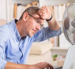 Schwitzender Büroarbeiter mit Ventilator