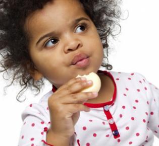 Kleines Mädchen beiem Essen eines Käsestücks