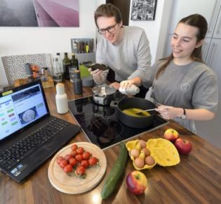 Computerlinguistik-Studenten Theresa Schmidt und Urs Peter beim Kochen mit KI-Unterstützung