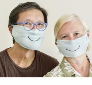 Paar mit Gesichtsmasken mit aufgemaltem Lächeln