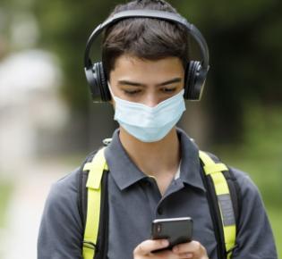 Teenager mit geschlossenem Kopfhörer und Smartphone in den Händen