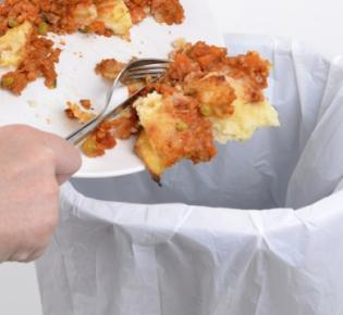 Speisereste werden in einen Mülleimer entsorgt