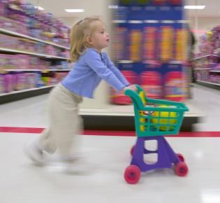 Kleines Mädchen mit Kindereinkaufswagen