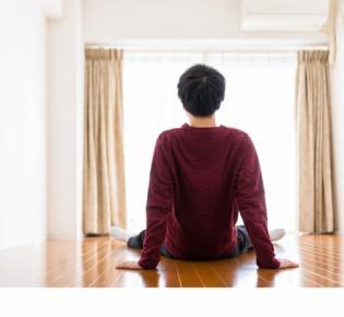 Rückenansicht eines auf dem Boden sitzenden Mannes in einem leeren Zimmer