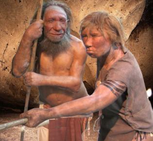 Neandertaler-Modellfiguren vor Höhlenwand