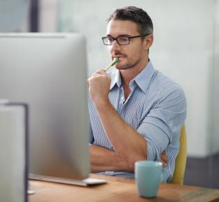 Mann an Computerarbeitsplatz