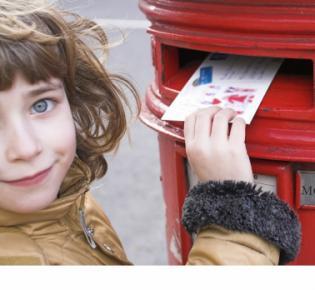 Mädchen beim Einwerfen einer Postkarte