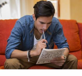 Mann beim Lösen eines Kreuzworträtsels
