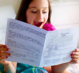 Schülerin blickt freudig überrascht auf ihr Schulzeugnis