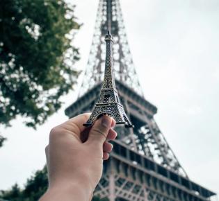 Hand mit Souvenir-Eiffelturm, der vor das Original gehalten wird