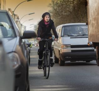 Radfahrerin zwischen Automobilen