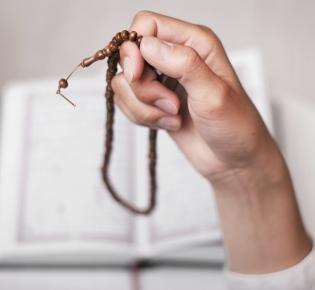 Hand mit Gebetskette vor aufgeschlagenem Koran