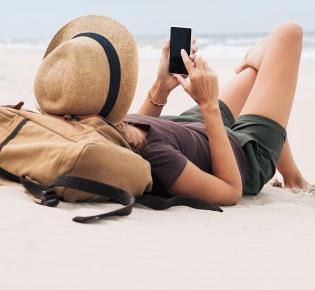 Frau benutzt Smartphone am Strand