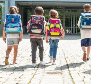 Rückenansicht von Schülern mit Schulranzen