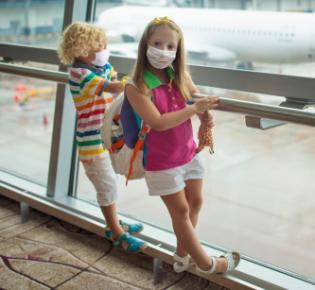 Zwei maskentragende Kinder am Fenster eines Flughafens