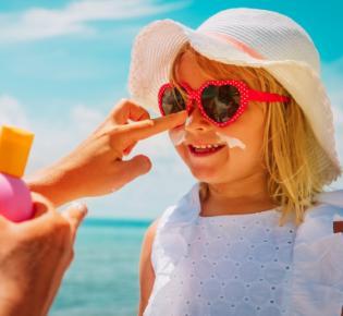 Kleines Mädchen beim Eincremen mit Sonnenöl