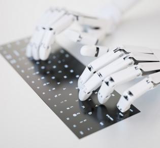 Roboterhände und Computertastatur