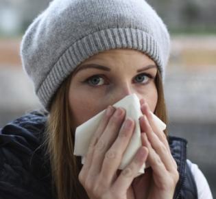 Junge Frau, sich die Nase putzend