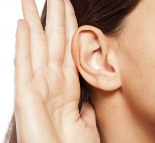 Ohr mit zum Lauschen angelegter Hand