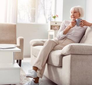 Kaffeetrinkende Seniorin in ihrem Wohnzimmer