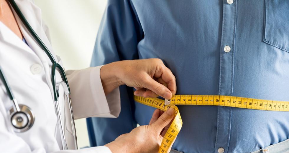 Massband um den Bauch eines übergewichtigen Mannes