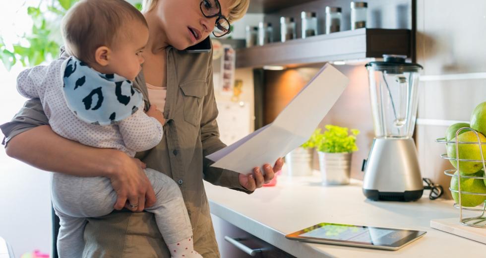 Mutter mit Kleinkind bei Telefongespäch