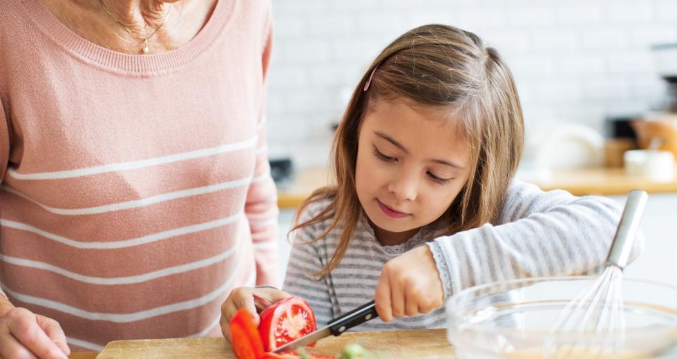 Kleines Mädchen beim Tomatenschneiden