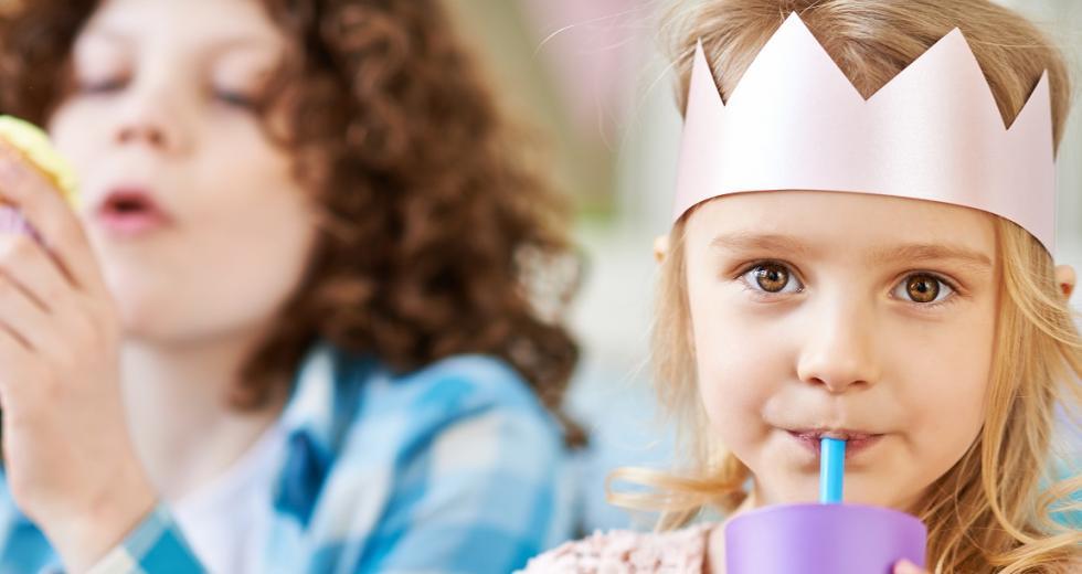 Mädchen mit Papierkrone und Becher mit softdrink