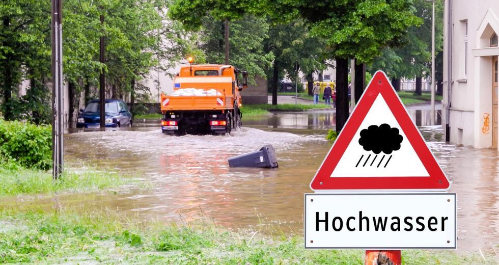 Überflutete Straße mit fiktivem Warnschild