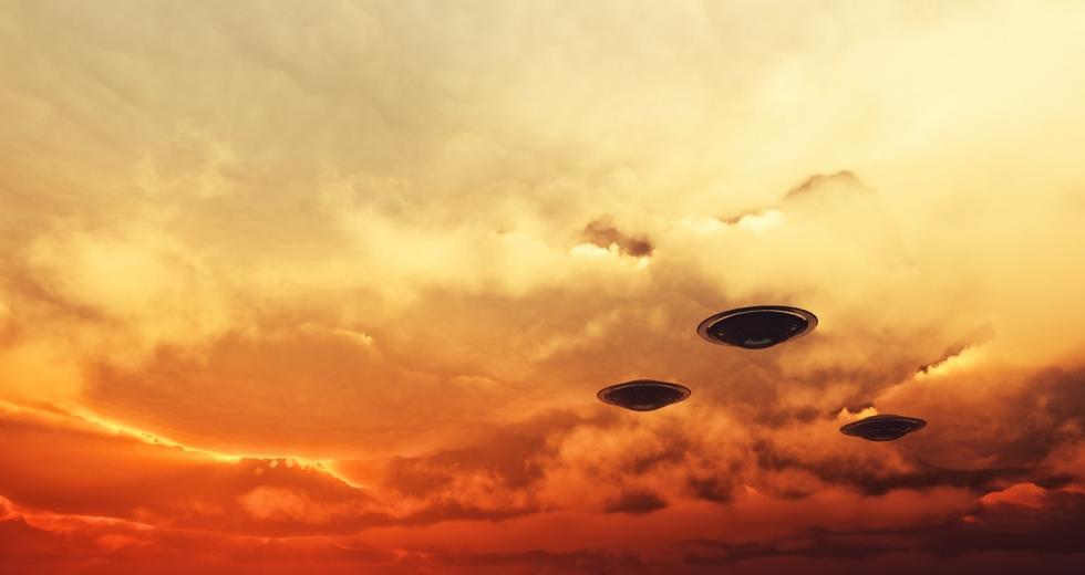 Drei Fliegende Untertassen vor rötlicher Wolkendecke