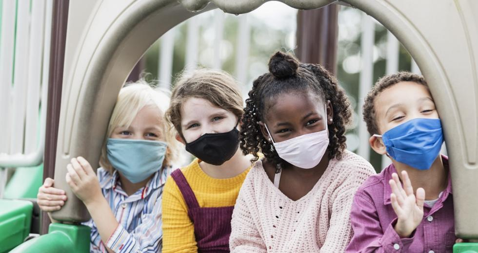 Kinder mit Maske auf einer Schaukel