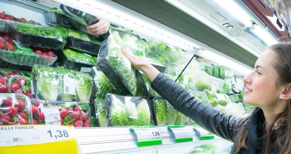 Junge Frau an einem Supermarktregal mit abgepacktem Salat