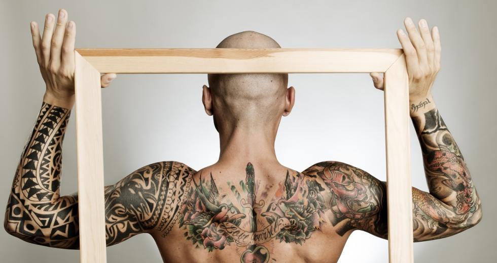 Bilderrahmen vor dem tätowierten Rücken eines Mannes