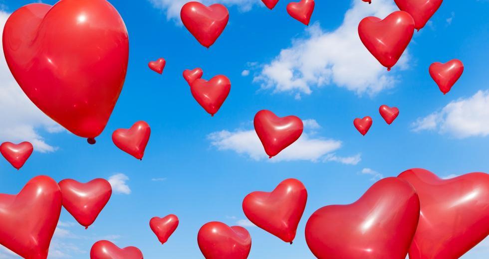 Rote Luftballonherzen vor blauem Himmel