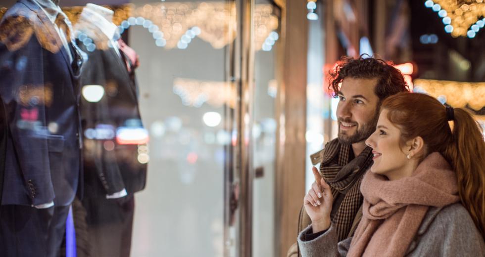 Junges Paar vor weihnachtlich dekoriertem Schaufenster