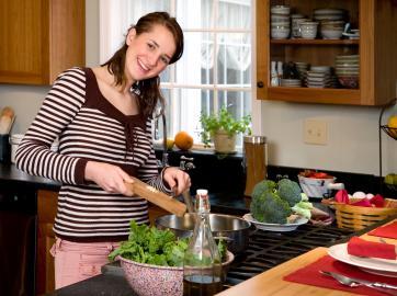 Frau gießt Öl an Salat