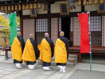 Vier buddhistische Mönche beten vor dem Tempel von Kyoto in Japan