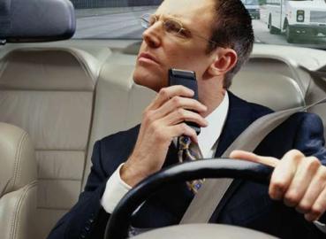 Mann rasiert sich am Steuer seines Autos